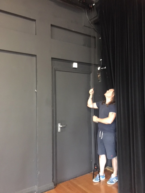 photo of person operating stage curtain
